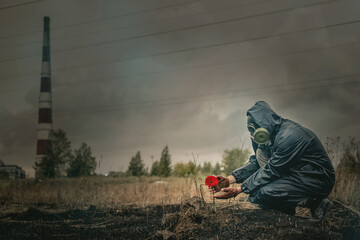 A man in gas mask and red gerbera flower on the burnt land background.