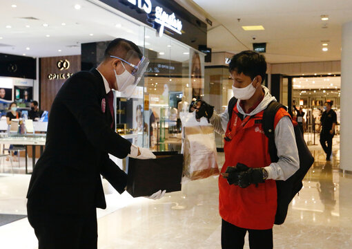 A staff member wearing a face shield and protective mask provides a paper bag to replace plastic at a Grand Indonesia shopping mall in Jakarta