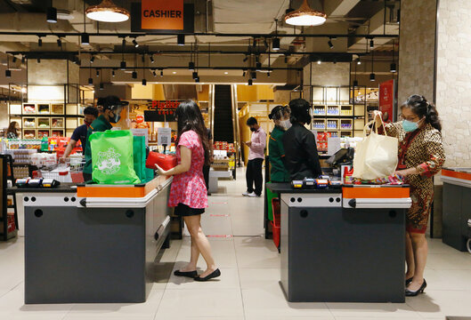 Customers use tote bags to replace plastic during shopping at a supermarket in Jakarta