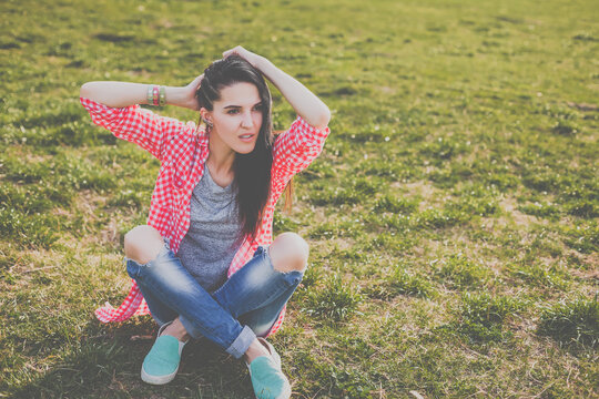 cute hipster woman sitting on the meadow. Looking at camera. Positive human emotion facial expression body language, concept of funny girl. Dressed in a gray t-shirt, and a shirt in a red cage