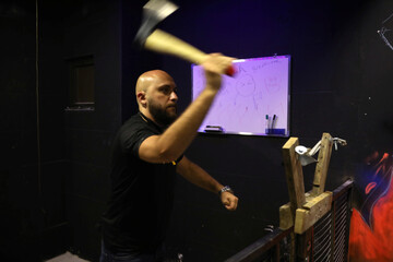 Aladdin Attari, founder and managing director of AXE Rage Rooms, throws an axe at a target at his store in Amman