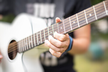 Acoustic Guitar Playing. A man plays the guitar against the background of nature.