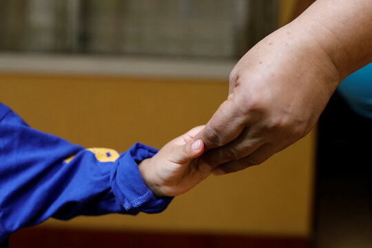An unaccompanied child who was deported from the U.S. touches hands with his carer at a shelter in Guatemala City