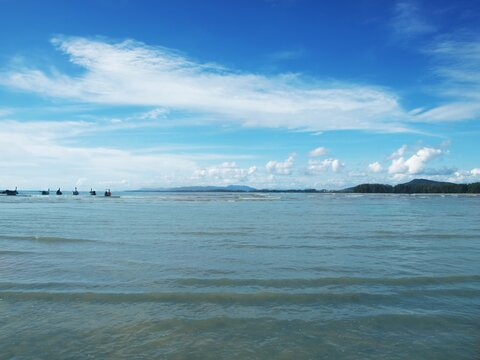 Muddy water with algae near the coast, shallow water, ebb. Bright blue sky with stunning white clouds. Small waves. Green forest on the horizon. Boats anchored on a distance from shore. Seascape. Sea
