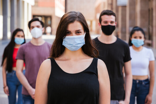 Portrait of a multiracial group of friends with masks in protection from Coronavirus infections, Covid-19 - Leader woman with other millennials behind her with serious eyes looking into the camera