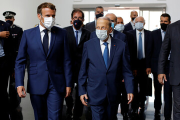 French President Emmanuel Macron and Lebanese President Michel Aoun walk side by side at Beirut airport