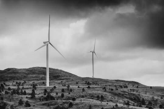 Windfarm in Norway in stormy weather with dark sky in black and white.