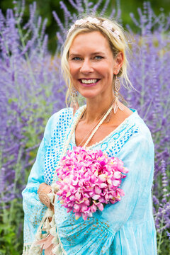 blond woman in her 40s standing in field of purple flowers