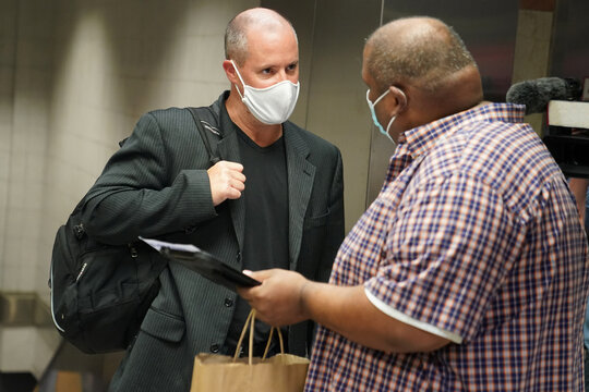 A man is questioned by officials at Penn Station as part of an effort to screen out-of-state travellers and enforce the state's 14-day coronavirus disease (COVID-19) quarantine, in New York City