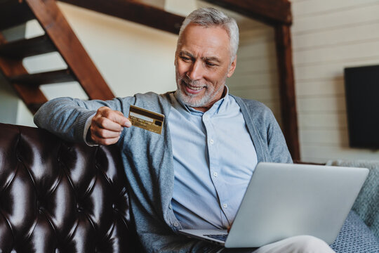 Happy senior man using laptop and holding credit card while sitting on sofa