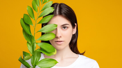 Natural beauty. Skin care. Portrait of woman covering fresh clean face with exotic green leaf isolated on orange copy space. Aesthetic cosmetology. Organic mask.