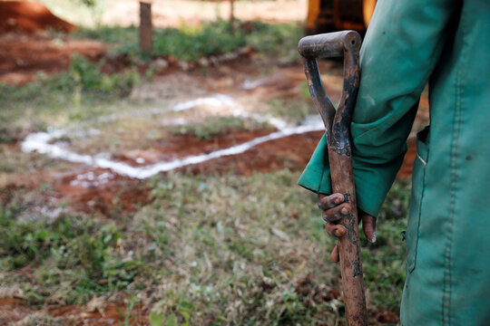 A grave digger holds a shovel near the chalk marks where a new grave is due to be dug, at the separated section of the muslim cemetery, in Nairobi