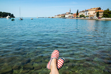 Woman's feet with espadrilles hanging over the transparent Adriatic sea water with croatian Rovinj city and boats on the background