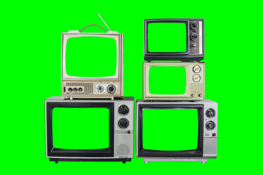 Five vintage televisions on old wood table with green screens and backgrounds.