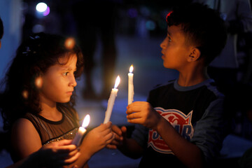 Palestinians light candles to mourn the victims of Tuesday's blast in Beirut's port area