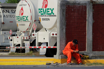 A worker of the Mexican state oil firm PEMEX is pictured during a protest against Senator Samuel Garcia's proposal to close down the Cadereyta refinery as a measure to lower the levels of pollution in the air, in Cadereyta
