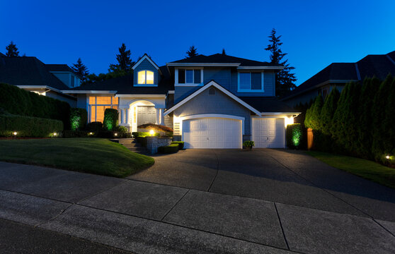 Suburban home exterior on a summer late evening with lights on yard and house