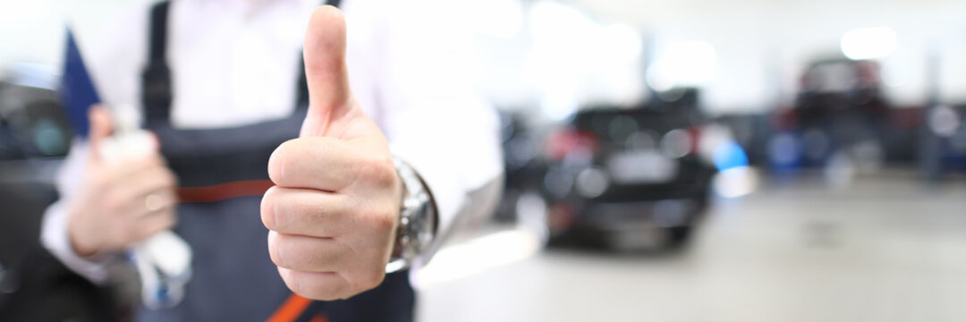 Close-up of person showing thumbs up. Good job and well done symbol. Copy space in right side. Mechanic in uniform posing in garage. Repair service station and handyman concept