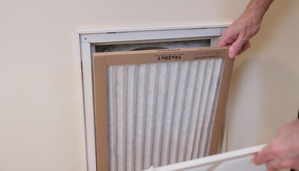 Replacing dirty central air conditioning  air filter.  HVAC repair technician performing maintenance on home indoor heating and cooling system. Air duct ventilation system maintenance for clean air.
