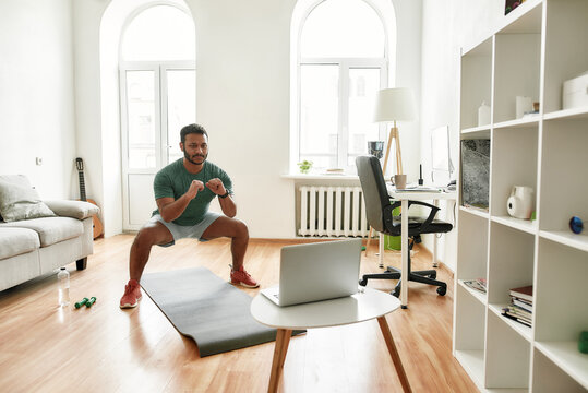 Healthy way of life. Full length shot of male fitness instructor showing exercises while streaming, broadcasting video lesson on training at home using laptop. Sport, online gym concept