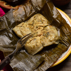 Mexican tamales in banana leaves on wooden background