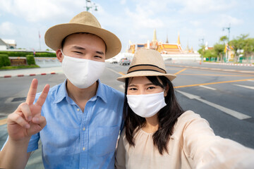 Asian couple happy tourists to travel wearing mask to protect from Covid-19 on they holidays and...