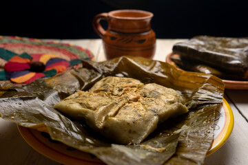Mexican tamales in banana leaves on white background