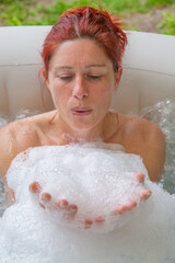 Pretty natural redheaded woman relaxing in her jacuzzi