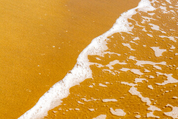 wave foam with golden sand on the ocean's edge