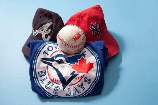 Blue Jays shirt, Braves and Yankees caps against a blue background