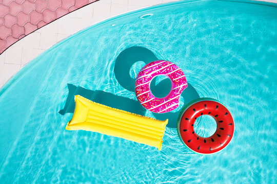 Inflatable rings and mattress floating in swimming pool, top view. Summer vacation