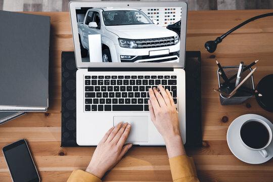 Buying online. Woman choosing car using laptop, top view