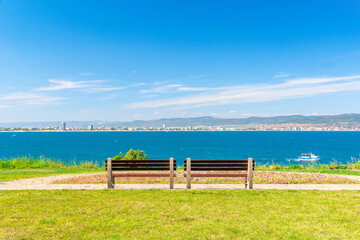 two benches on the sunny beach shore. beautiful view from paved footpath on the seaside. city and mountain in the distance beneath a blue sky with clouds