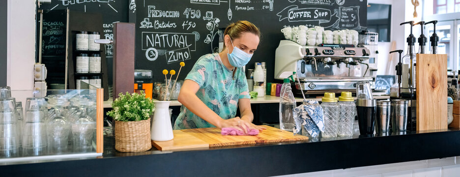 Waitress with mask disinfecting the bar counter due to coronavirus