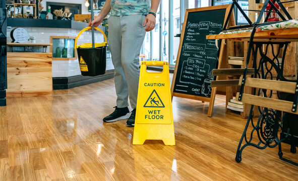 Worker placing wet floor sign after mopping the floor