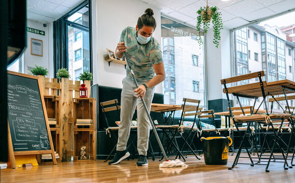 Worker with mask mopping the floor of a restaurant
