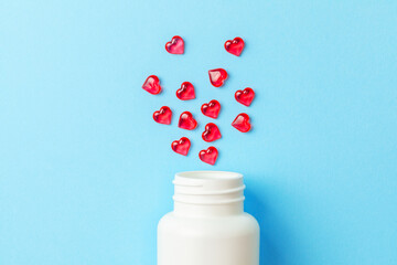Pills of love. Red pills in the shape of heart with bottle on blue background