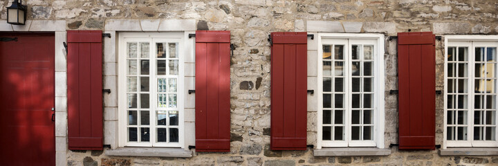 Facade of an old stone house with window and brown shutters. Panoramic image