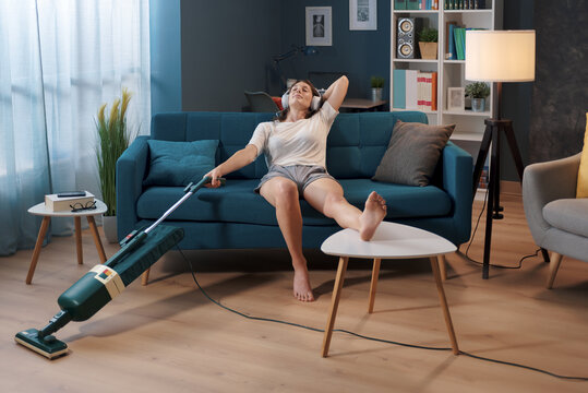 Lazy housewife procrastinating chores, she is resting on the sofa and holding the vacuum cleaner