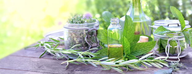 leaf of aromatic plant with glass jar and oil in a bottle arranged on a table in a garden
