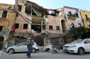 A man walks past rubble of damaged buildings following Tuesday's blast at Beirut's port area