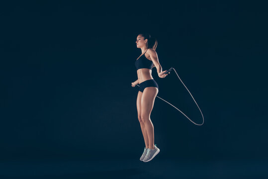 Full length body size profile side view of her she nice attractive sportive strong slim thin adorable lady working out jumping up in air isolated over black background