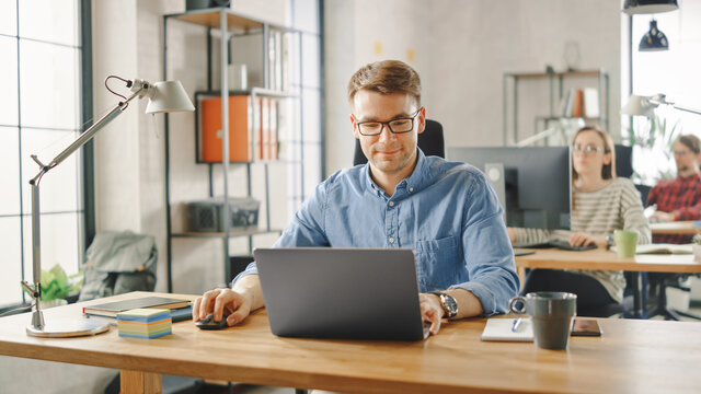 Handsome Young Man in Glasses and Shirt is Working on a Laptop in a Creative Business Agency. They Work in Loft Office. Diverse People Working in the Background. He's in Good Mood.