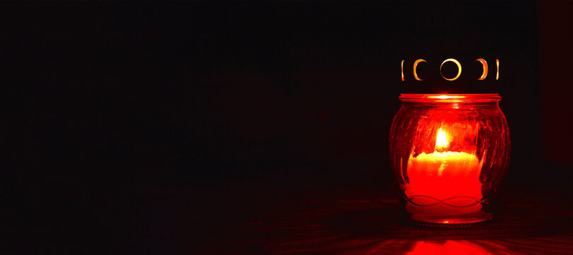 All Saints Day candle. Red votive candle on dark background