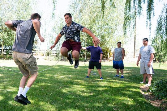 College football team members jumping rope in a rural backyard