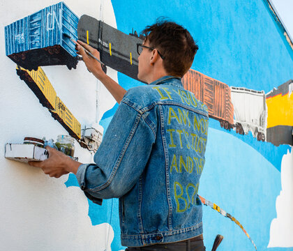 Artists Creating a Train Mural on the Side of a Building