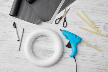 A set of objects for handcrafted creativity - making of festive wreath for Halloween on a gray wooden background. Flat lay
