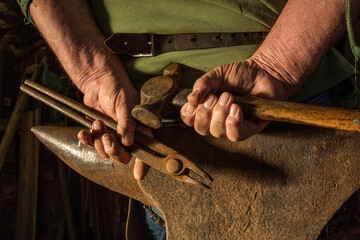 A farrier's hands clasped above an anvil