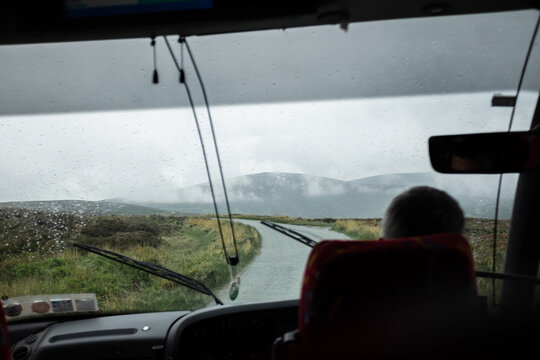 Tour bus on rainy day with hills