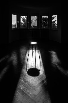 Small stool in an empty room in early morning light, black and white